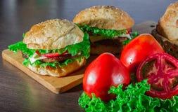 Κινηματογράφηση σε πρώτο πλάνο των κατ' οίκον γίνοντων νόστιμων burgers στον ξύλινο πίνακα Στοκ Εικόνες