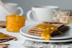 Κινηματογράφηση σε πρώτο πλάνο των καφετιών σουηδικών κροτίδων ψωμιού σίκαλης τραγανών με την πορτοκαλιά μαρμελάδα Στοκ Εικόνες