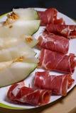 Κινηματογράφηση σε πρώτο πλάνο των κυλημένων φετών του θεραπευμένου ζαμπόν χοιρινού κρέατος jamon με το πεπόνι Στοκ Εικόνα