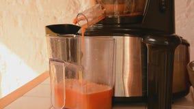 Κινηματογράφηση σε πρώτο πλάνο των μήλων και των καρότων επεξεργασίας juicer Στοκ Φωτογραφία