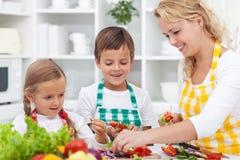 Κινηματογράφηση σε πρώτο πλάνο των νεαρών με τη μητέρα τους στην κουζίνα Στοκ Φωτογραφία