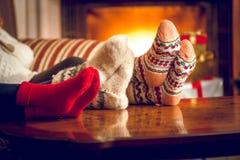 Κινηματογράφηση σε πρώτο πλάνο των οικογενειακών θερμαίνοντας ποδιών στην εστία Στοκ εικόνα με δικαίωμα ελεύθερης χρήσης