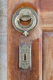 Κινηματογράφηση σε πρώτο πλάνο των παλαιών ρόπτρων πορτών χαλκού περίκομψων πέρα από μια ηλικίας ξύλινη πόρτα Στοκ Εικόνα