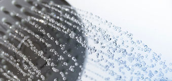 Κινηματογράφηση σε πρώτο πλάνο των πτώσεων ντους κεφαλιών και νερού Στοκ Εικόνα