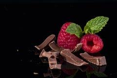 Κινηματογράφηση σε πρώτο πλάνο των σμέουρων με τα φύλλα μεντών και της σοκολάτας στο μαύρο β Στοκ φωτογραφία με δικαίωμα ελεύθερης χρήσης