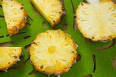 Κινηματογράφηση σε πρώτο πλάνο των φετών και του διχοτομημένου ανανά στο δίσκο στοκ εικόνες