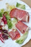 κινηματογράφηση σε πρώτο πλάνο των φετών του κυλημένου θεραπευμένου ζαμπόν χοιρινού κρέατος jamon με το μαρούλι Στοκ Εικόνες