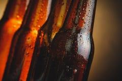 Κινηματογράφηση σε πρώτο πλάνο των φρέσκων κρύων μπουκαλιών αγγλικής μπύρας μπύρας με τις πτώσεις και το πώμα Στοκ Φωτογραφία