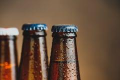 Κινηματογράφηση σε πρώτο πλάνο των φρέσκων κρύων μπουκαλιών αγγλικής μπύρας μπύρας με τις πτώσεις και την εστίαση στο πώμα Στοκ Φωτογραφία