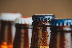 Κινηματογράφηση σε πρώτο πλάνο των φρέσκων κρύων μπουκαλιών αγγλικής μπύρας μπύρας με τις πτώσεις και την εστίαση στο πώμα Στοκ Φωτογραφίες