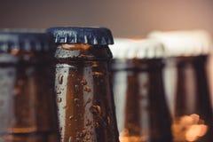 Κινηματογράφηση σε πρώτο πλάνο των φρέσκων κρύων μπουκαλιών αγγλικής μπύρας μπύρας με τις πτώσεις και την εστίαση στο πώμα Στοκ Εικόνες