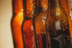 Κινηματογράφηση σε πρώτο πλάνο των φρέσκων κρύων μπουκαλιών αγγλικής μπύρας μπύρας με τις πτώσεις και το πώμα Στοκ φωτογραφία με δικαίωμα ελεύθερης χρήσης