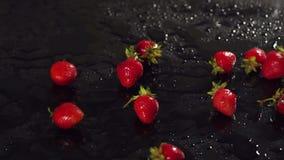 Κινηματογράφηση σε πρώτο πλάνο των φραουλών σε μια υγρή μαύρη επιφάνεια φιλμ μικρού μήκους