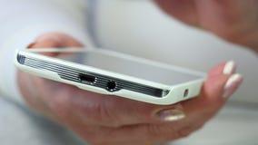 Κινηματογράφηση σε πρώτο πλάνο των χεριών γυναικών με το άσπρο smartphone φιλμ μικρού μήκους