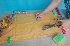 Κινηματογράφηση σε πρώτο πλάνο των χεριών γυναικών που ράβουν το κίτρινο ύφασμα υπαίθρια Στοκ Φωτογραφίες