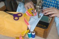 Κινηματογράφηση σε πρώτο πλάνο των χεριών γυναικών που ράβουν το κίτρινο ύφασμα υπαίθρια Στοκ εικόνες με δικαίωμα ελεύθερης χρήσης