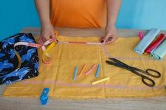 Κινηματογράφηση σε πρώτο πλάνο των χεριών γυναικών που ράβουν το κίτρινο ύφασμα υπαίθρια Στοκ Εικόνες