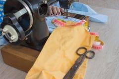 Κινηματογράφηση σε πρώτο πλάνο των χεριών γυναικών που ράβουν το κίτρινο ύφασμα υπαίθρια Στοκ Εικόνα