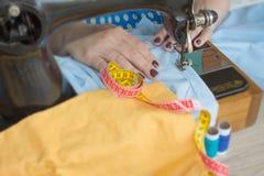 Κινηματογράφηση σε πρώτο πλάνο των χεριών γυναικών που ράβουν το κίτρινο ύφασμα υπαίθρια Στοκ φωτογραφία με δικαίωμα ελεύθερης χρήσης