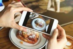 Κινηματογράφηση σε πρώτο πλάνο των χεριών γυναικών ` s που παίρνουν τη φωτογραφία του γλυκού επιδορπίου από το smartphone στοκ εικόνα