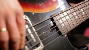 Κινηματογράφηση σε πρώτο πλάνο των χεριών μουσικών που παίζουν τη γρήγορη μουσική με τη βαθιά κιθάρα στη συναυλία φιλμ μικρού μήκους