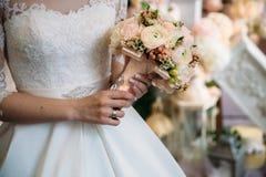 Κινηματογράφηση σε πρώτο πλάνο των χεριών νυφών που κρατούν την όμορφη γαμήλια ανθοδέσμη με τα άσπρα και ρόδινα τριαντάφυλλα Έννο Στοκ Φωτογραφία