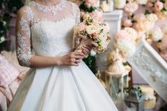 Κινηματογράφηση σε πρώτο πλάνο των χεριών νυφών που κρατούν την όμορφη γαμήλια ανθοδέσμη με τα άσπρα και ρόδινα τριαντάφυλλα Έννο Στοκ Εικόνες