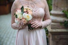Κινηματογράφηση σε πρώτο πλάνο των χεριών νυφών που κρατούν την όμορφη γαμήλια ανθοδέσμη με τα άσπρα και ρόδινα τριαντάφυλλα Έννο Στοκ φωτογραφία με δικαίωμα ελεύθερης χρήσης