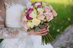 Κινηματογράφηση σε πρώτο πλάνο των χεριών νυφών που κρατούν την όμορφη γαμήλια ανθοδέσμη με τα άσπρα και ρόδινα τριαντάφυλλα Έννο Στοκ Εικόνα