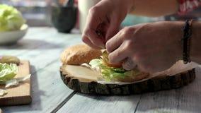 Κινηματογράφηση σε πρώτο πλάνο των χεριών που κατασκευάζουν cheeseburger απόθεμα βίντεο