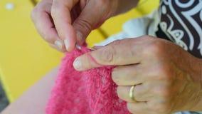 Κινηματογράφηση σε πρώτο πλάνο των χεριών της ηλικιωμένης γυναίκας που πλέκουν το κόκκινο μαλλί απόθεμα βίντεο
