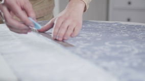Κινηματογράφηση σε πρώτο πλάνο των χεριών seamstress Ντυμένη στην ύφασμα τέμνουσα γραμμή απόθεμα βίντεο
