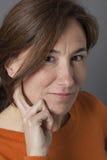 Κινηματογράφηση σε πρώτο πλάνο, φυσικά προκλητική μέση ηλικίας γυναίκα που χαμογελά με τη χειρονομία χεριών Στοκ Φωτογραφία