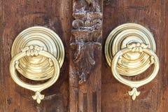 Κινηματογράφηση σε πρώτο πλάνο δύο παλαιών ρόπτρων πορτών χαλκού περίκομψων πέρα από μια ηλικίας ξύλινη περίκομψη πόρτα Στοκ φωτογραφία με δικαίωμα ελεύθερης χρήσης