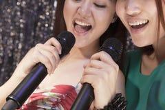Κινηματογράφηση σε πρώτο πλάνο δύο φίλων που κρατούν τα μικρόφωνα και που τραγουδούν μαζί στο καραόκε Στοκ Εικόνες