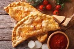 Κινηματογράφηση σε πρώτο πλάνο calzone πιτσών σε χαρτί και τα συστατικά οριζόντια κορυφή Στοκ Φωτογραφία