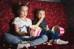 Κινηματογράφος παιδιών: Ένα κορίτσι και ένα αγόρι προσέχουν έναν κινηματογράφο στο σπίτι σε έναν μεγάλο κόκκινο καναπέ στο σκοτάδ στοκ φωτογραφίες με δικαίωμα ελεύθερης χρήσης