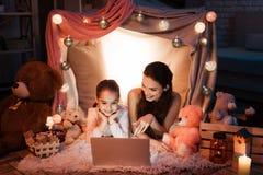 Κινηματογράφος προσοχής μητέρων και κορών στο lap-top στο σπίτι μαξιλαριών αργά τη νύχτα στο σπίτι Στοκ φωτογραφία με δικαίωμα ελεύθερης χρήσης