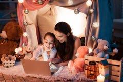 Κινηματογράφος προσοχής μητέρων και κορών στο lap-top στο σπίτι μαξιλαριών αργά τη νύχτα στο σπίτι Στοκ εικόνες με δικαίωμα ελεύθερης χρήσης