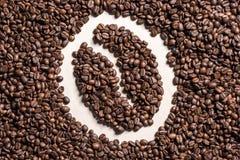 Κινηματογραφήσεων σε πρώτο πλάνο άποψη του συμβόλου φασολιών καφέ που γίνεται τοπ από τα ψημένα σιτάρια καφέ Στοκ Εικόνες