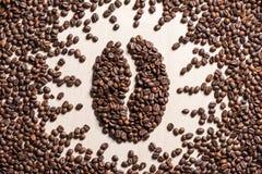 Κινηματογραφήσεων σε πρώτο πλάνο άποψη του συμβόλου φασολιών καφέ που γίνεται τοπ από τα ψημένα σιτάρια καφέ Στοκ Φωτογραφίες