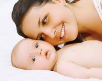 Κινηματογραφήσεων σε πρώτο πλάνο mom και μωρό πορτρέτου ευτυχές στο κρεβάτι στοκ εικόνα