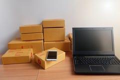 Κινητά τηλέφωνο, lap-top, και κιβώτιο προϊόντων, στο ξύλινο πάτωμα, on-line που ψωνίζει, εργασία στο σπίτι στοκ εικόνα με δικαίωμα ελεύθερης χρήσης
