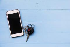 Κινητά τηλέφωνο και αυτοκίνητο μακρινά κλειδιά στο ξύλινο υπόβαθρο Στοκ φωτογραφία με δικαίωμα ελεύθερης χρήσης