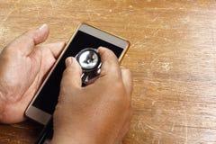 Κινητή έννοια υγείας - χέρι που επιθεωρεί ένα smartphone χρησιμοποιώντας ένα ste Στοκ Φωτογραφία