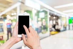Κινητή εικόνα τηλεφώνων και θαμπάδων χρήσης κοριτσιών μέσα στη λεωφόρο Στοκ εικόνες με δικαίωμα ελεύθερης χρήσης