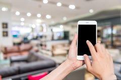 Κινητή εικόνα τηλεφώνων και θαμπάδων χρήσης κοριτσιών μέσα στη λεωφόρο Στοκ Εικόνες