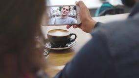 Κινητή τηλεοπτική κλήση Τηλέφωνο με το πρόσωπο στην οθόνη στην κινηματογράφηση σε πρώτο πλάνο χεριών απόθεμα βίντεο