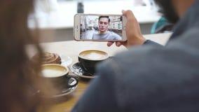 Κινητή τηλεοπτική κλήση Τηλέφωνο με το πρόσωπο στην οθόνη στην κινηματογράφηση σε πρώτο πλάνο χεριών φιλμ μικρού μήκους