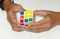 Κινητός κύβος Rubik ` s σε ένα άσπρο υπόβαθρο με την πείρα Και χ Στοκ Εικόνες
